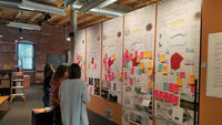 Poster boards are pinned up on a wall for architects to view.