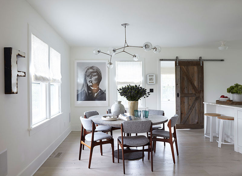 a dining area with a reclaimed barn door in the background