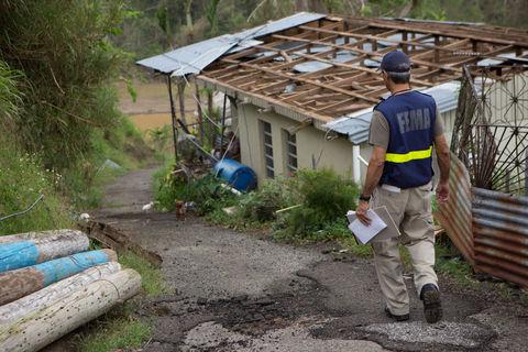 A FEMA worker checks on a survivor of Hurricane Maria, whose home was damaged in Utuado, Puerto Rico.
