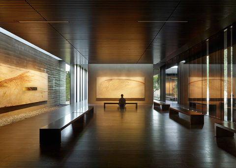 A visitor sits in a warmly lit gallery space.